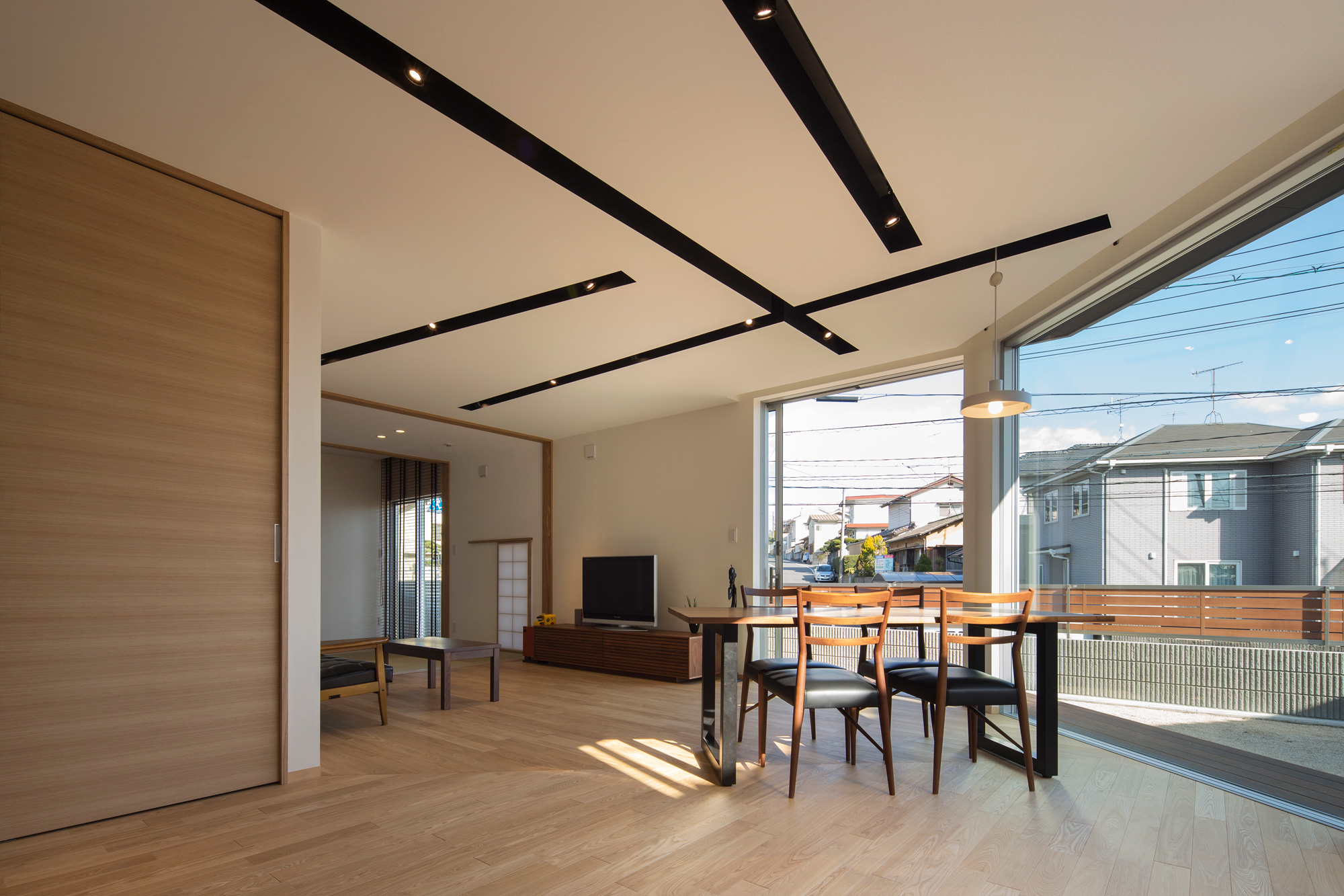 キッチンからリビングダイニングを見る: 天井照明を黒いボックスのなかに仕込み、LDKのカタチを強調するデザインです