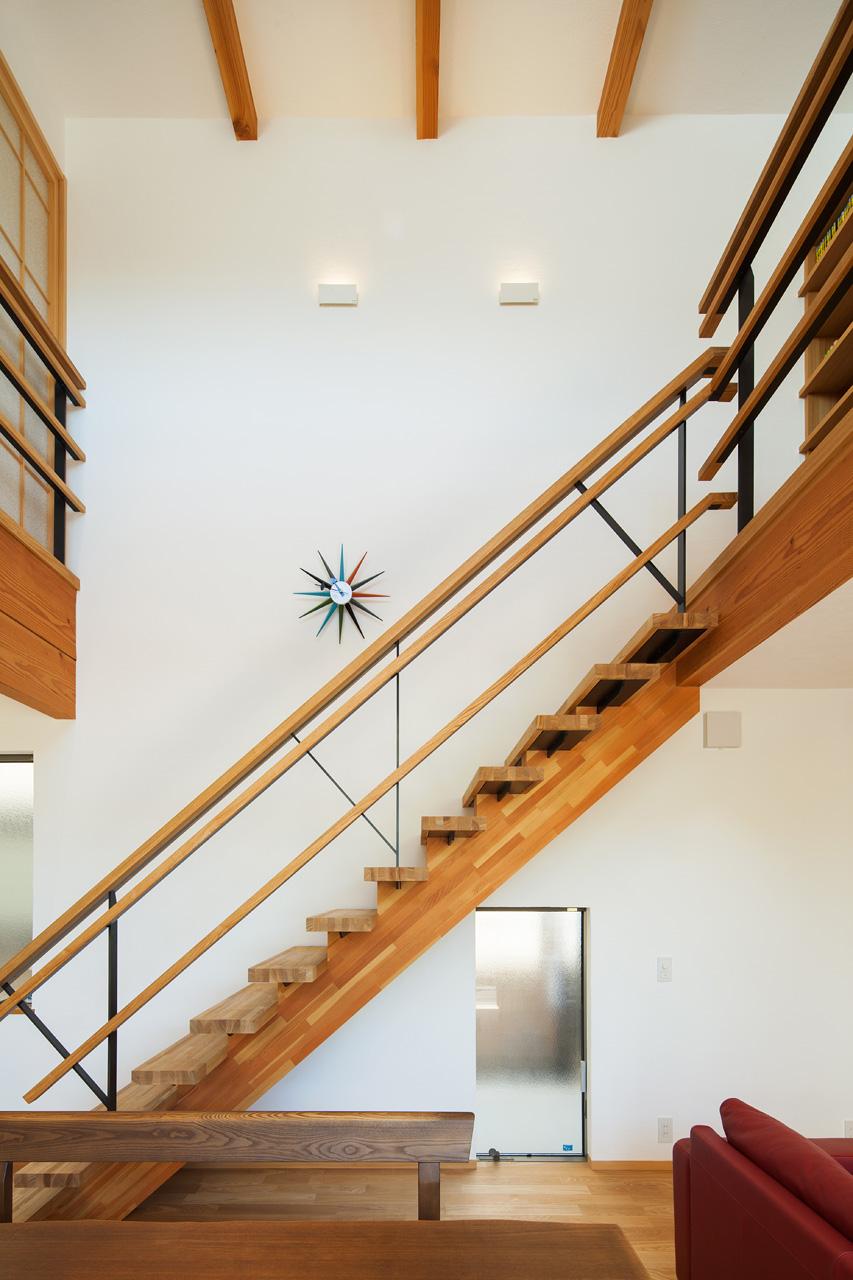 吹抜けと階段: デザインされた階段と手摺が、リビングのインテリアとしての役割も果たしています