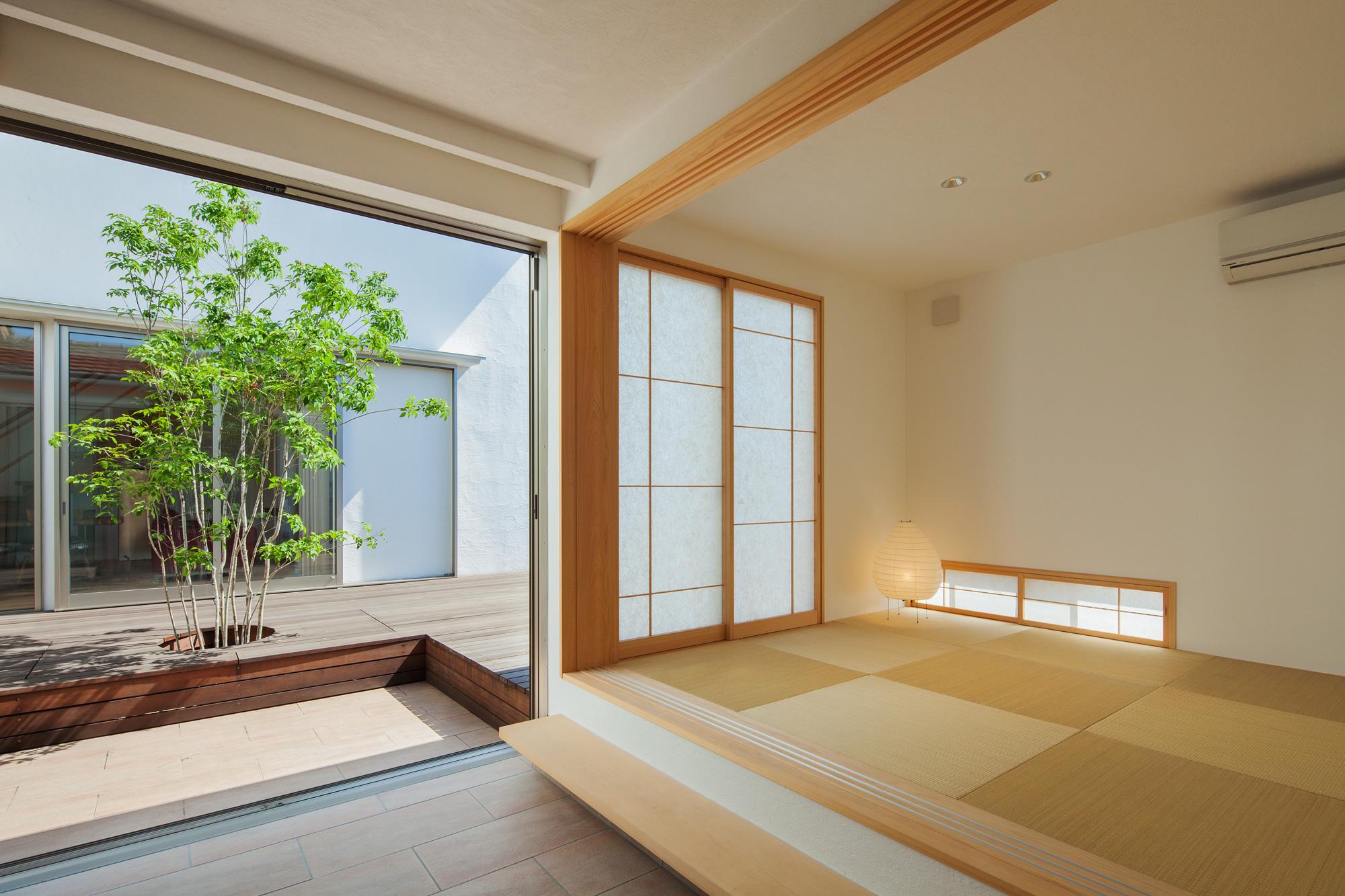 玄関から客間・中庭を望む: 全開放できるサッシと襖を開けると、玄関・客間・中庭がひとつの空間となります。自由度が高く、さまざまな使い勝手が考えられる空間です