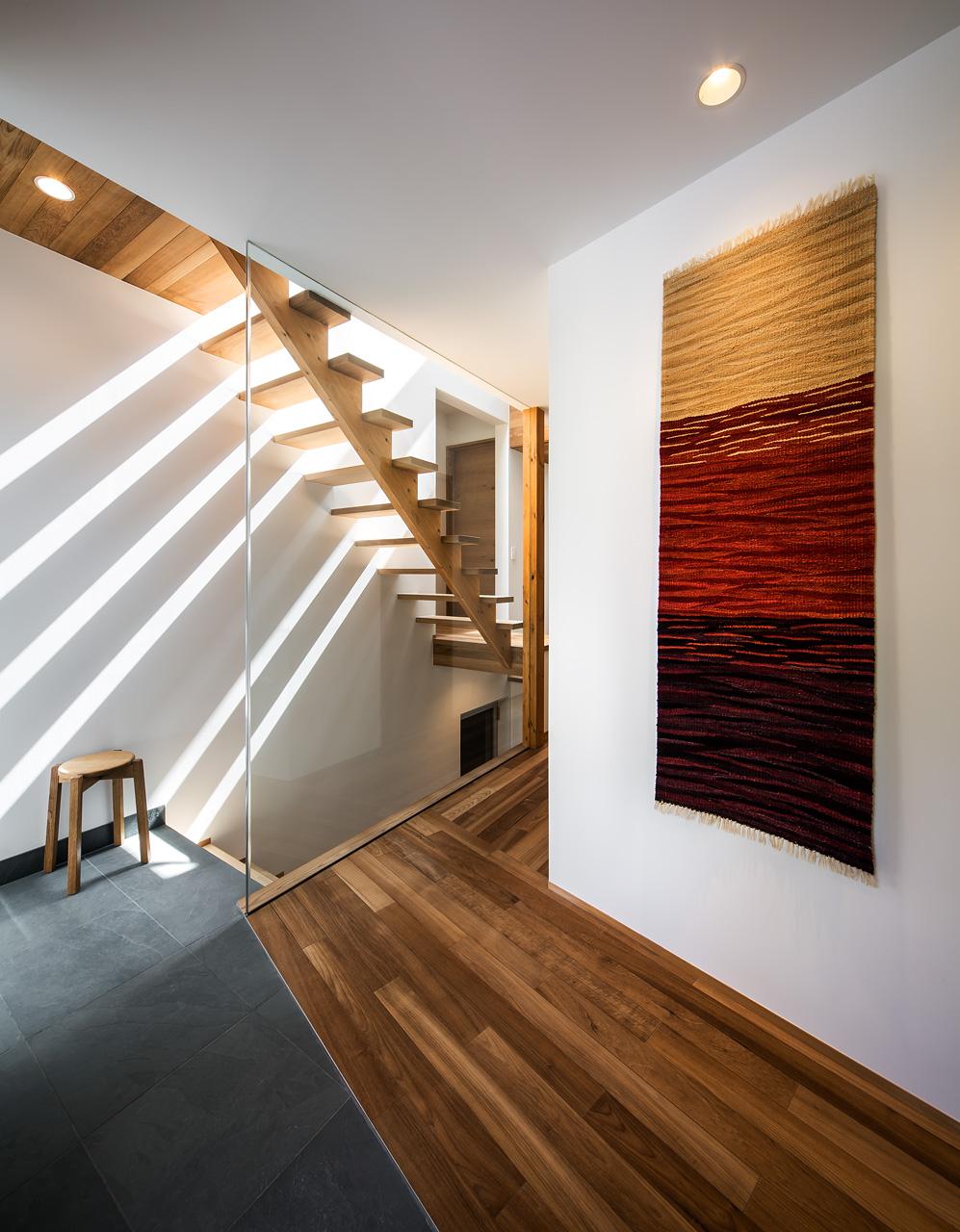 エントランス:地階の駐車場から直接玄関へ上がれる階段があります。クレバスからの光を遮らないように、廊下との仕切りはガラス製です