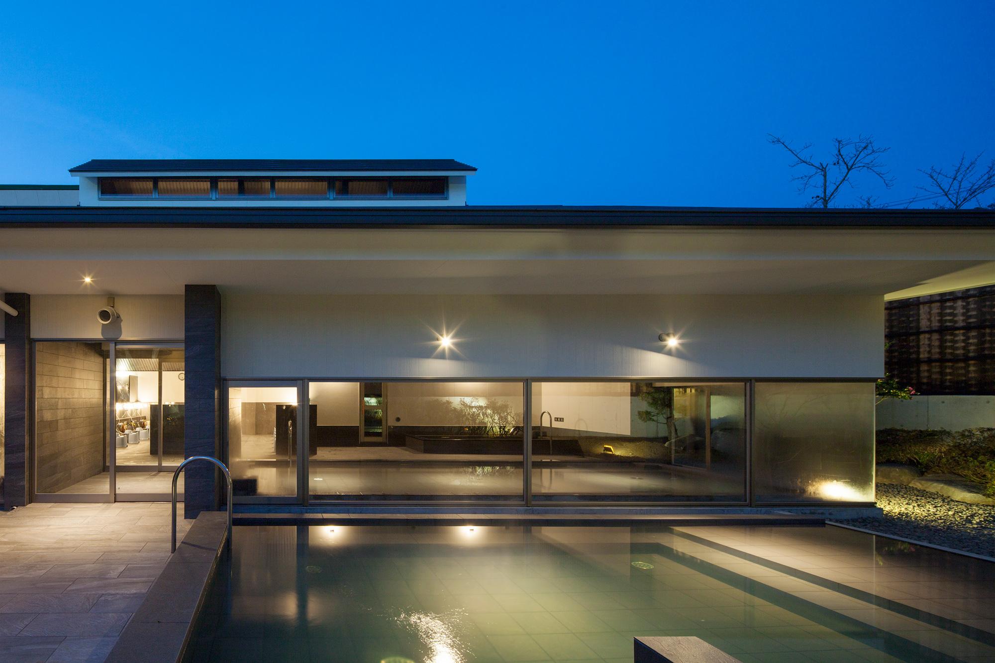 夕景: 深い庇と低い窓で、水平方向の広がりを感じられる建物に