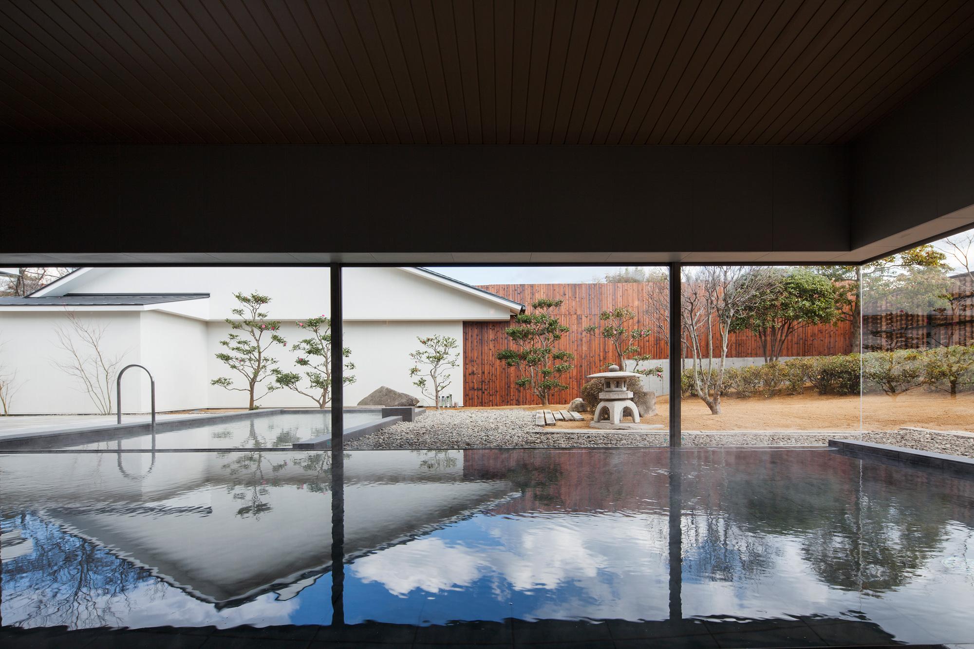 内部から庭を見る: 外部の景色が水面に映り込み、内と外の境界を曖昧にします