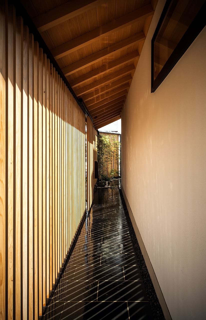 玄関口からエントランス方面をのぞむ: 内と外の間にある空間。差しこむ光がうつくしい陰影をつくりだします。その奥には[格子とヤマボウシの庭]が