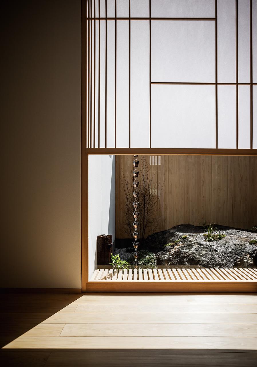 廊下から[陸ガメの暮らす大岩]: 雪見障子によって視線を低くおさえ、個室への視線をコントロールしています
