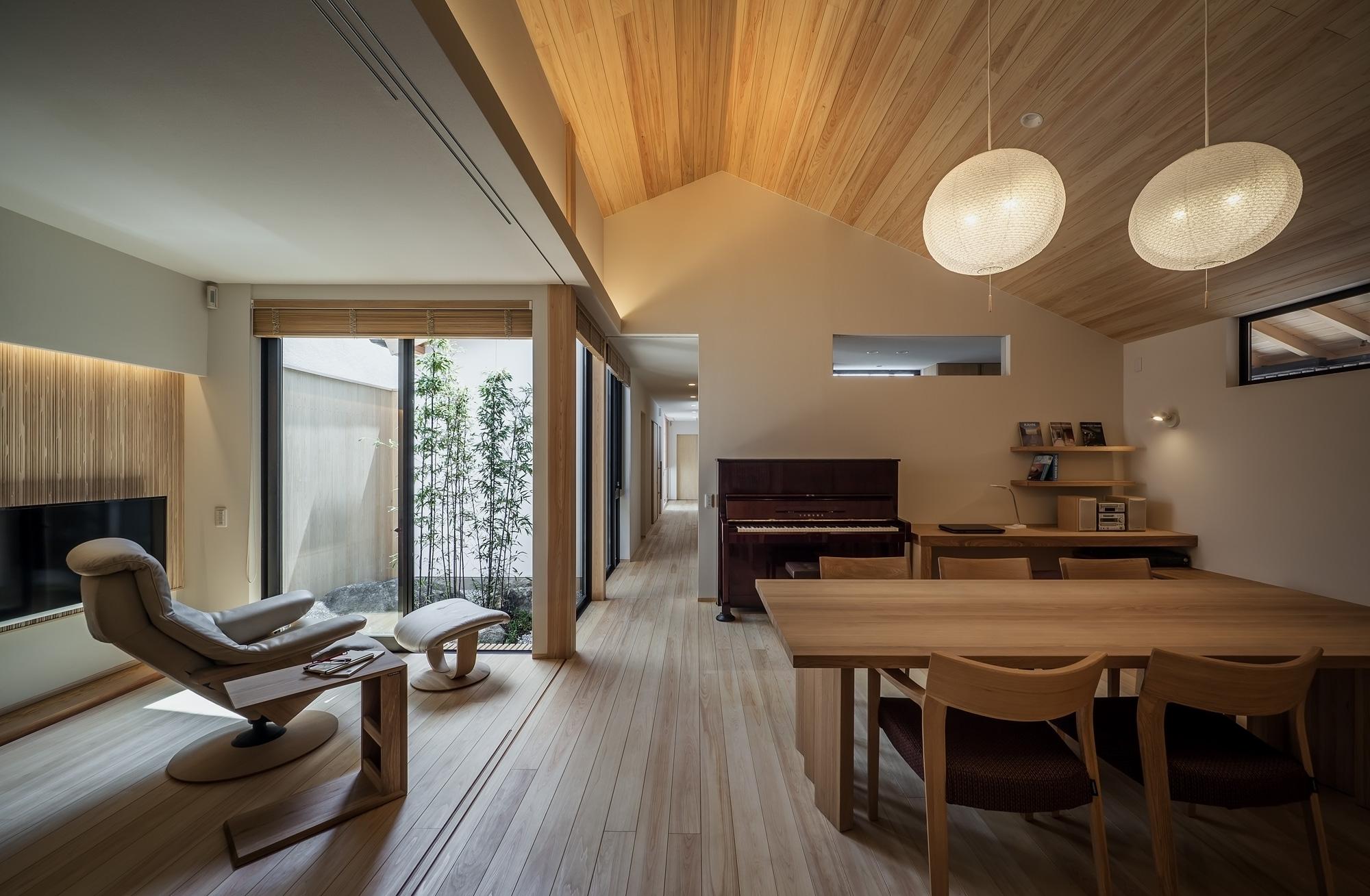 ダイニングと居間: [黒竹と苔むす岩の庭]に面した家族の集うリビング・ダイニング。一体の空間となっている居間は、引き戸を締めれば客間として機能します