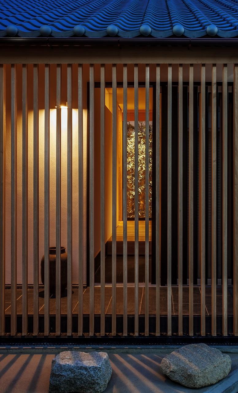 西面夕景: 玄関の扉を開けると、街路から縦格子ごしに[黒竹と苔むす岩]まで見通すことができます
