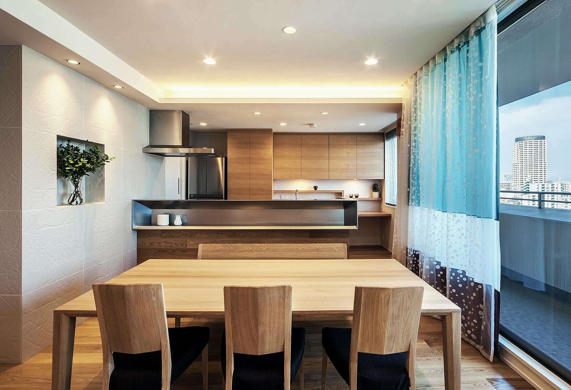 リビングよりキッチンを見る: タモのナチュラルな色合いをベースに、様々な素材で空間を構成しています。カーテンは美しい柄のレースを内側にかけるレースインスタイル。ドレープの色の組合せや高さは特注です