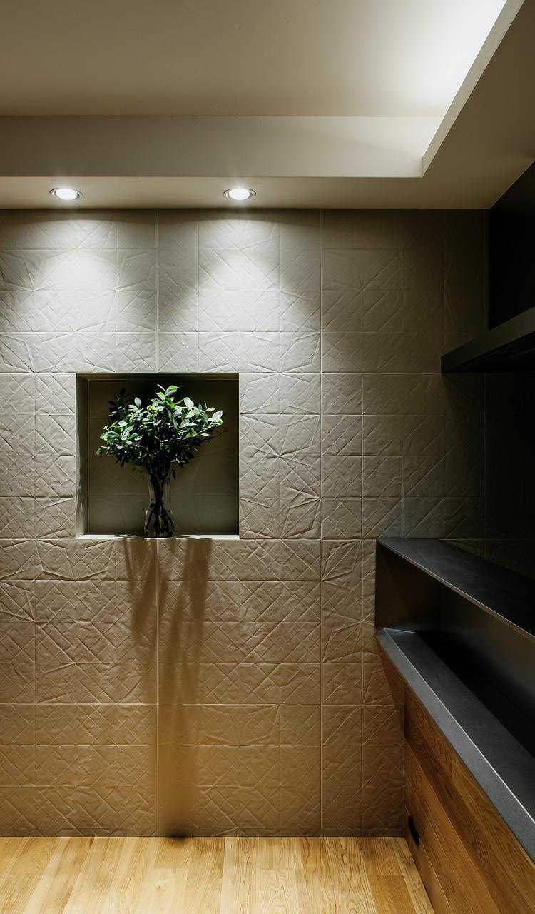 リビングの壁: タイルながら、折り曲げた紙のテクスチャーが堅さのない自然で優しい風合いを空間に与えてくれます。ダウンライトを壁際に配置し、その素材感を強調しています