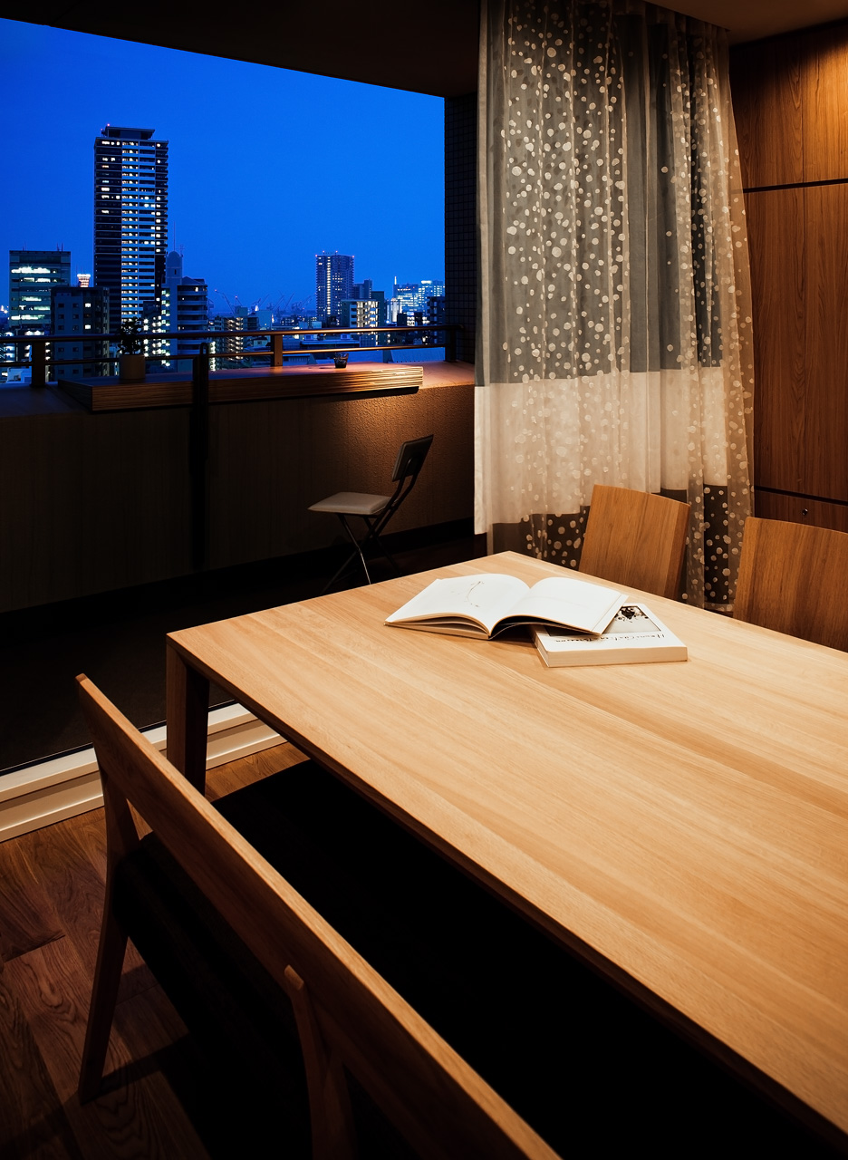 リビングからバルコニーを見る: バルコニーには、神戸の夜景を見ながら晩酌できるよう、カウンターを設けました。余った床材を置いただけの簡易なものですが、外部空間は積極的に使いたいと思っています