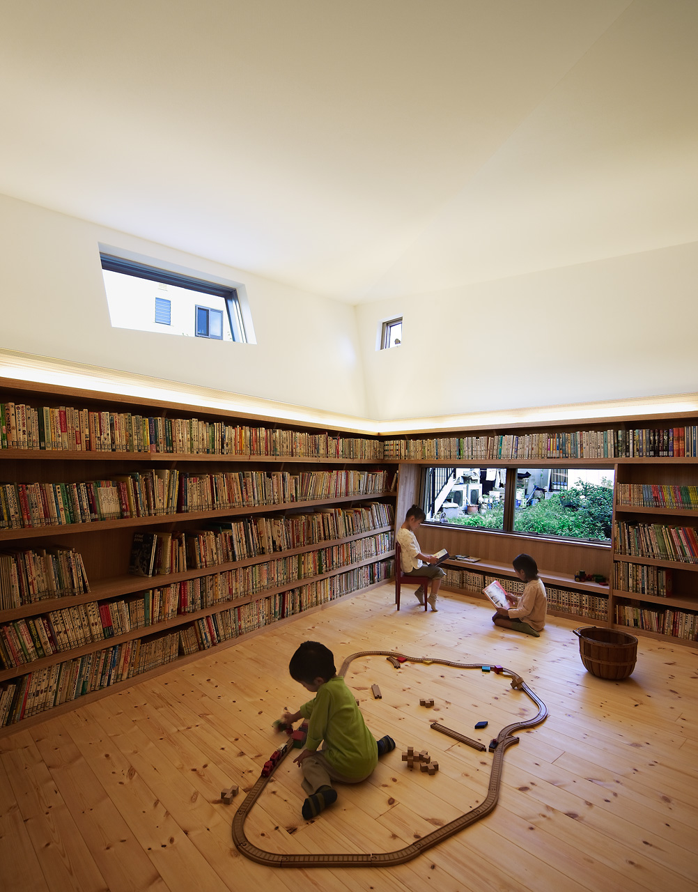 絵本ルーム: 30年間に収集された5200冊の絵本が壁一面に並びます。照明はモアレ現象を利用したグラフィカルで遊びのあるデザインの間接照明を用いました。子供のスケールに合わせた窓からは緑豊かな空地を望むことができます