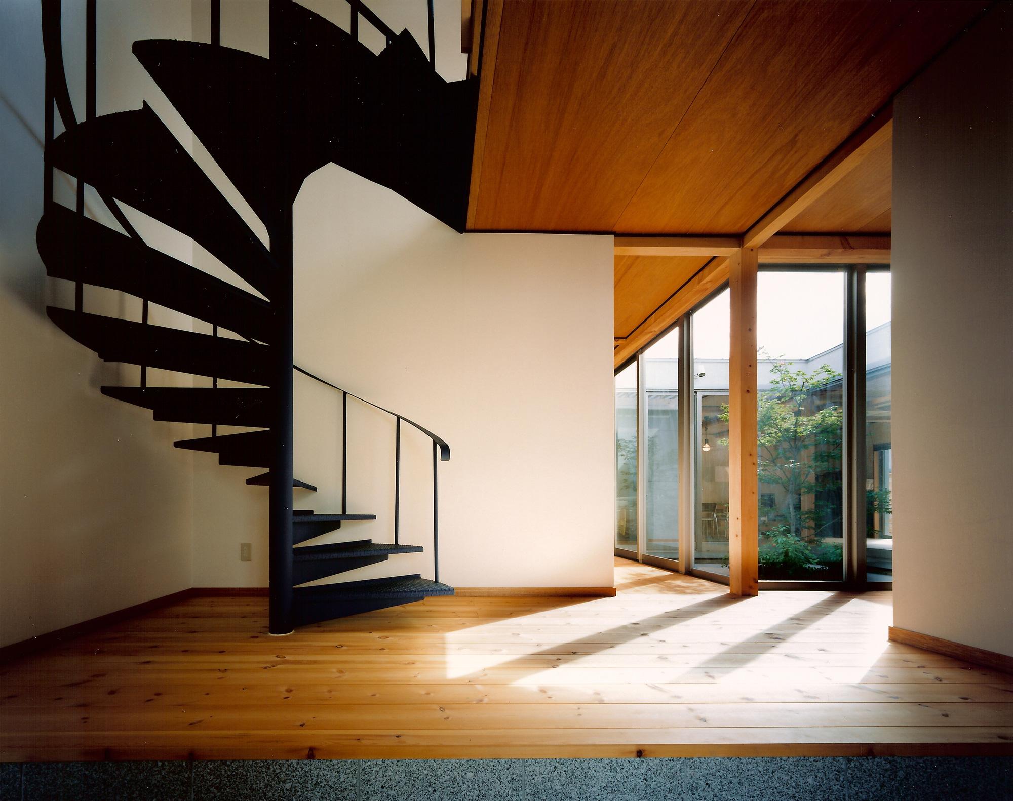 エントランス: 戸をくぐると中庭のノムラモミジ、その奥にLDKを見通すことができます。階段は生活時間の異なる長女の個室に繋がっており、玄関から直接アクセスできるようになっています
