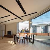 <p> キッチンからリビングダイニングを見る: 天井照明を黒いボックスのなかに仕込み、LDKのカタチを強調するデザインです </p>