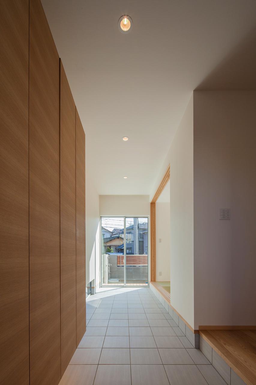 玄関から通り土間を見る: 「上足」と「下足」の間の空間。さまざまな使い方が可能です。右手奥には和室が見えます