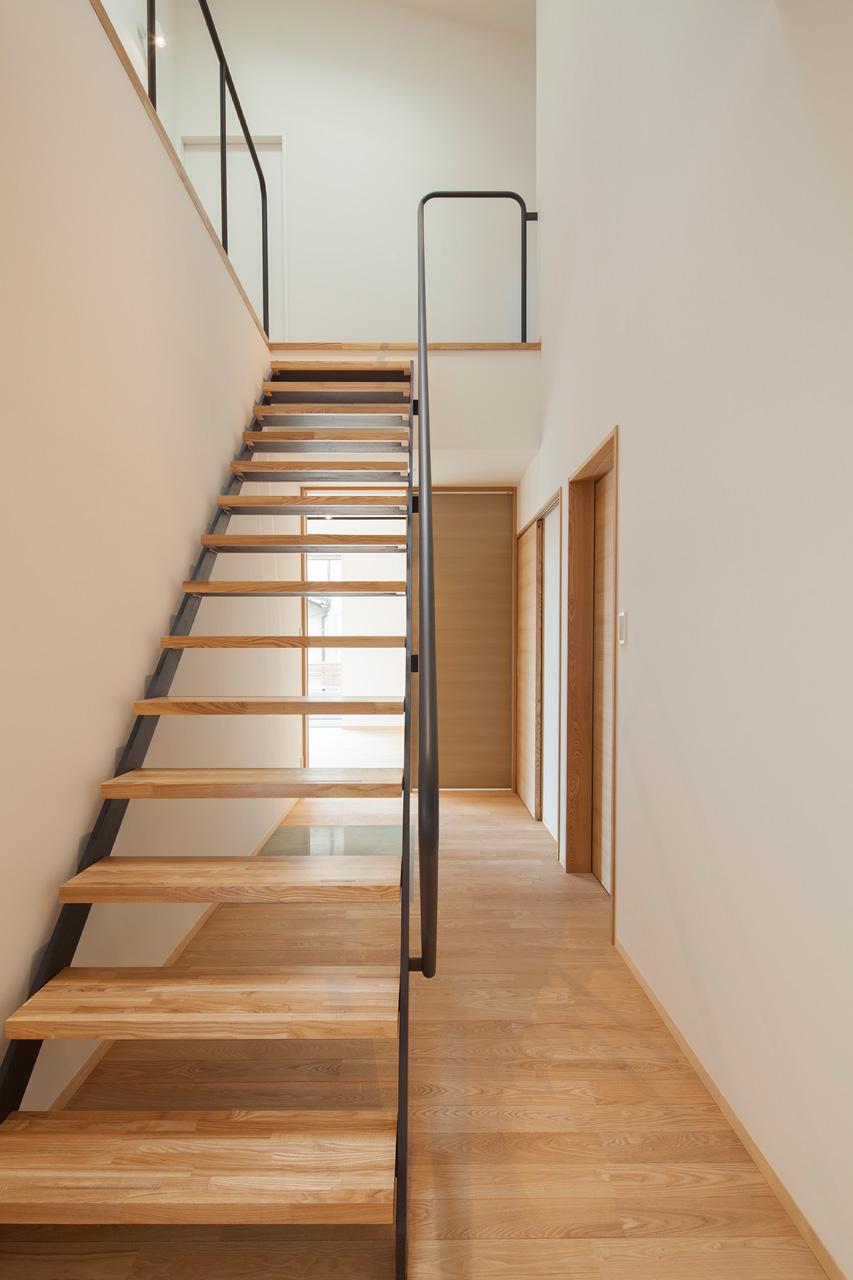 玄関から階段ホールを見る: 階段は透け感のある軽やかなデザインとしました