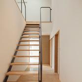<p> 玄関から階段ホールを見る: 階段は透け感のある軽やかなデザインとしました </p>