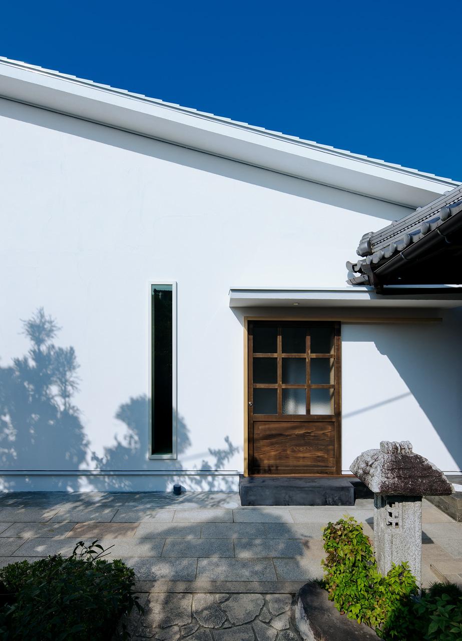 東面の玄関: 東面には母屋との行き来がしやすいように、もうひとつの玄関をつくりました。扉にはもとからあった蔵戸を再利用し、新しい住まいに記憶の連続性をもたせています