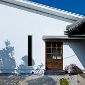 <p> 東面の玄関: 東面には母屋との行き来がしやすいように、もうひとつの玄関をつくりました。扉にはもとからあった蔵戸を再利用し、新しい住まいに記憶の連続性をもたせています </p>