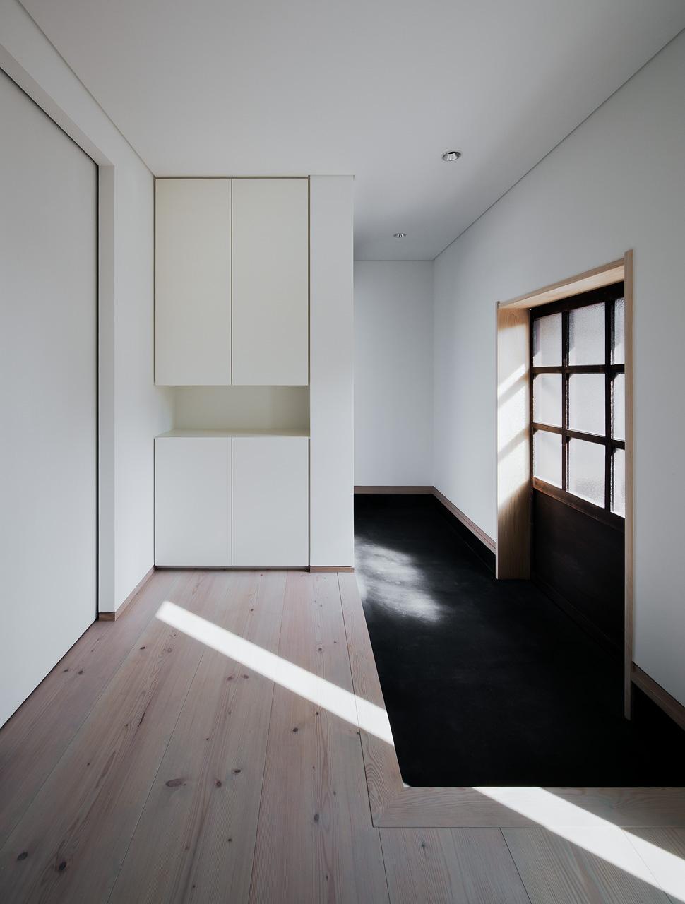 玄関内部: 右手には母屋へ続く蔵戸、奥には若夫婦専用の扉と、人が行き交う場所であることから、「溜め」の空間としてデザインしました