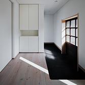 <p> 玄関内部: 右手には母屋へ続く蔵戸、奥には若夫婦専用の扉と、人が行き交う場所であることから、「溜め」の空間としてデザインしました </p>