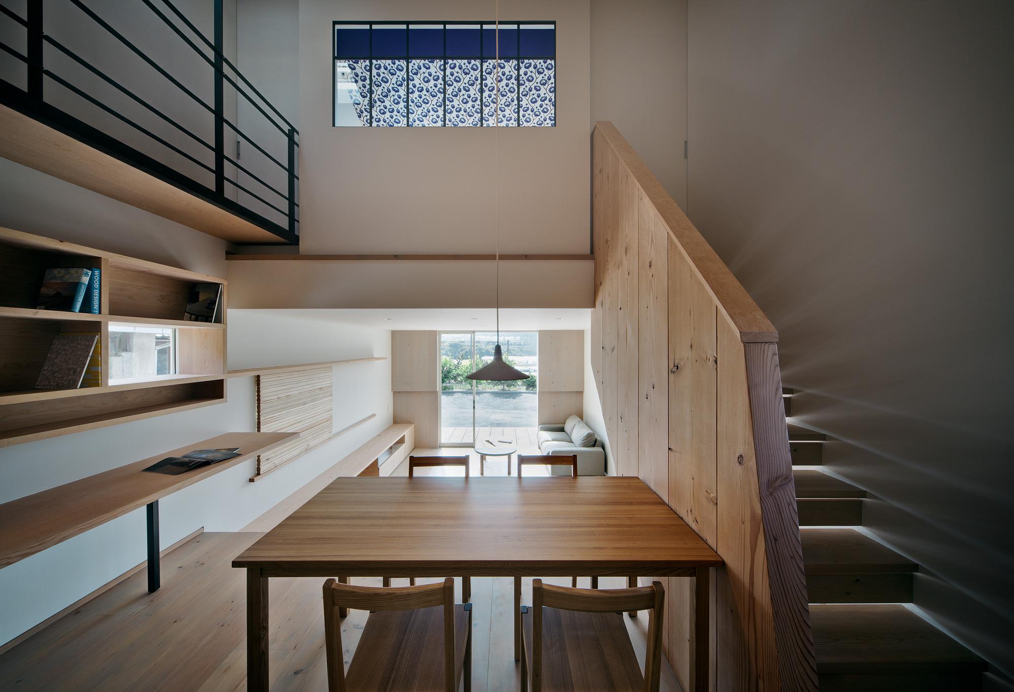 キッチンから吹き抜け/LDKを望む: 1階は敷地の勾配をいかし、700mmの高低差をつけています。キッチンに立つと、ダイニングルームやリビングルーム、吹き抜け越しの寝室と、空間のすべてを一望することができます