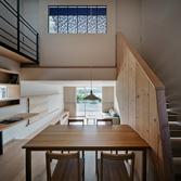 <p> キッチンから吹き抜け/LDKを望む: 1階は敷地の勾配をいかし、700mmの高低差をつけています。キッチンに立つと、ダイニングルームやリビングルーム、吹き抜け越しの寝室と、空間のすべてを一望することができます </p>