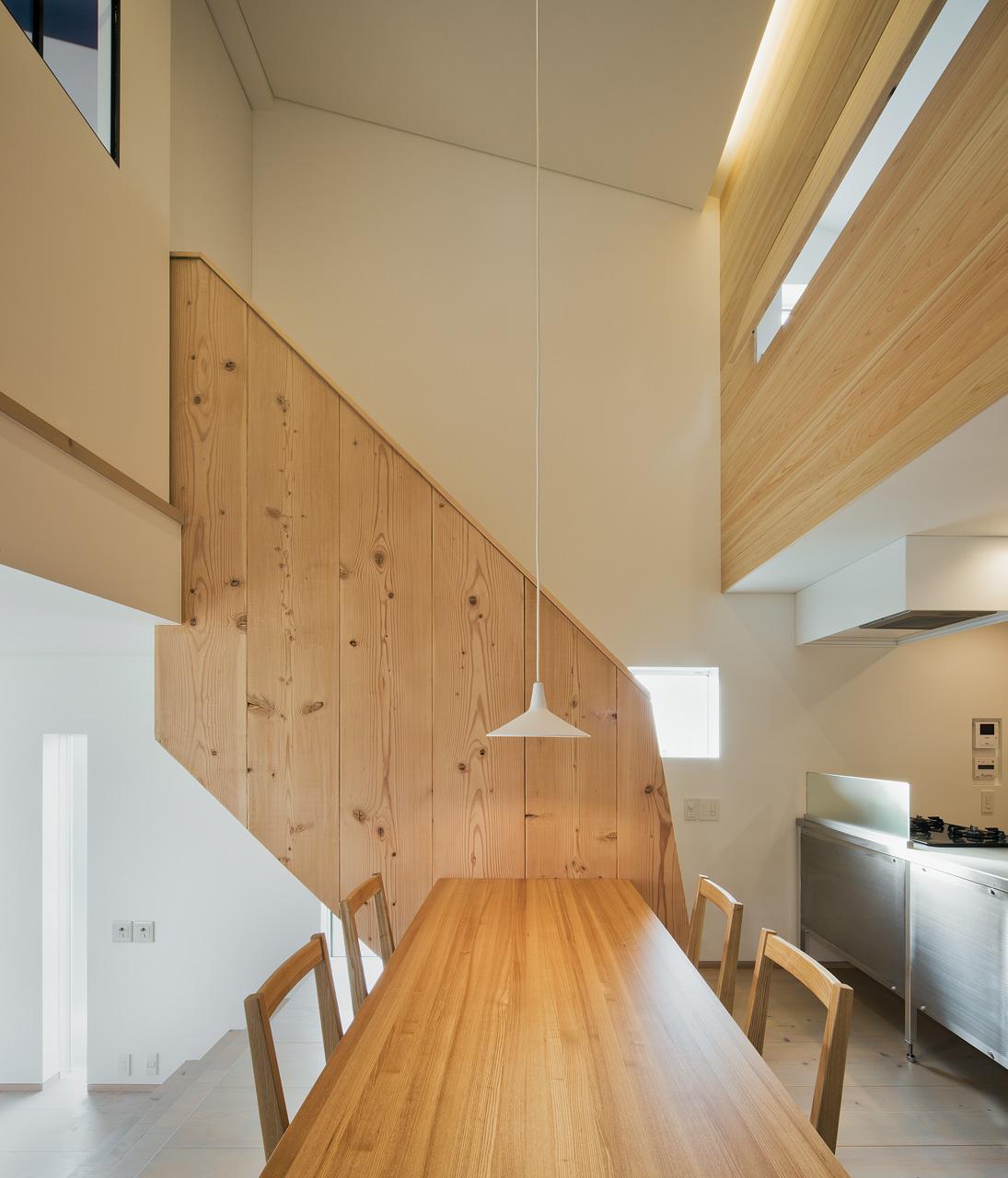 ダイニングルームから階段を見る: 階段の手摺も米松の梁材をボルトでつなぎ合わせてつくり、無垢材の重量感と暖かみを感じられるようにしました