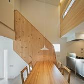 <p> ダイニングルームから階段を見る: 階段の手摺も米松の梁材をボルトでつなぎ合わせてつくり、無垢材の重量感と暖かみを感じられるようにしました </p>