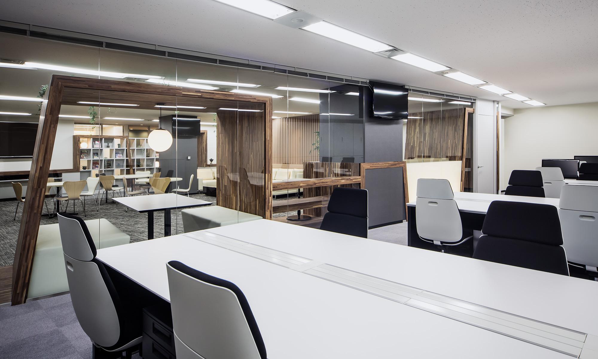 執務室からラウンジをみる: 執務室とラウンジは、ガラスと帯家具で仕切られています