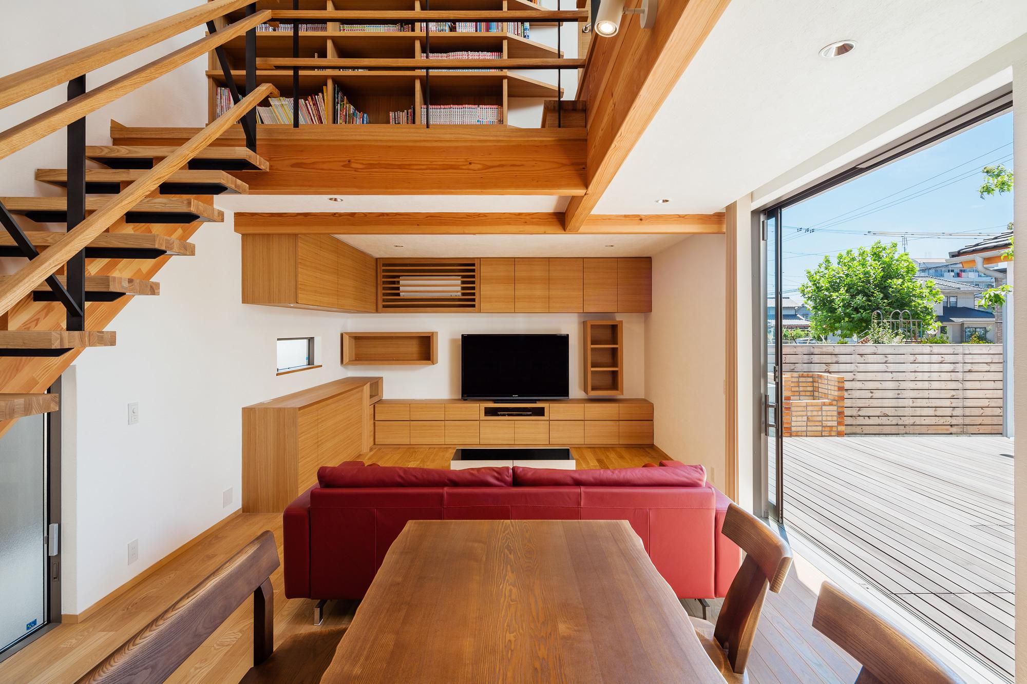 リビング: インテリアは木目の美しいタモ材を使い、壁や天井も自然素材である漆喰を用いてナチュラルで優しい雰囲気に。上階のブリッジには書棚をつくりつけています