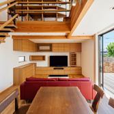 <p> リビング: インテリアは木目の美しいタモ材を使い、壁や天井も自然素材である漆喰を用いてナチュラルで優しい雰囲気に。上階のブリッジには書棚をつくりつけています </p>