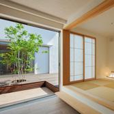 <p> 玄関から客間・中庭を望む: 全開放できるサッシと襖を開けると、玄関・客間・中庭がひとつの空間となります。自由度が高く、さまざまな使い勝手が考えられる空間です </p>