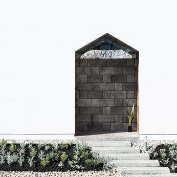 <p> アプローチとエントランス: 建物の切妻をなぞったようなエントランスの開口部。背後の桜並木を見通すことができます </p>