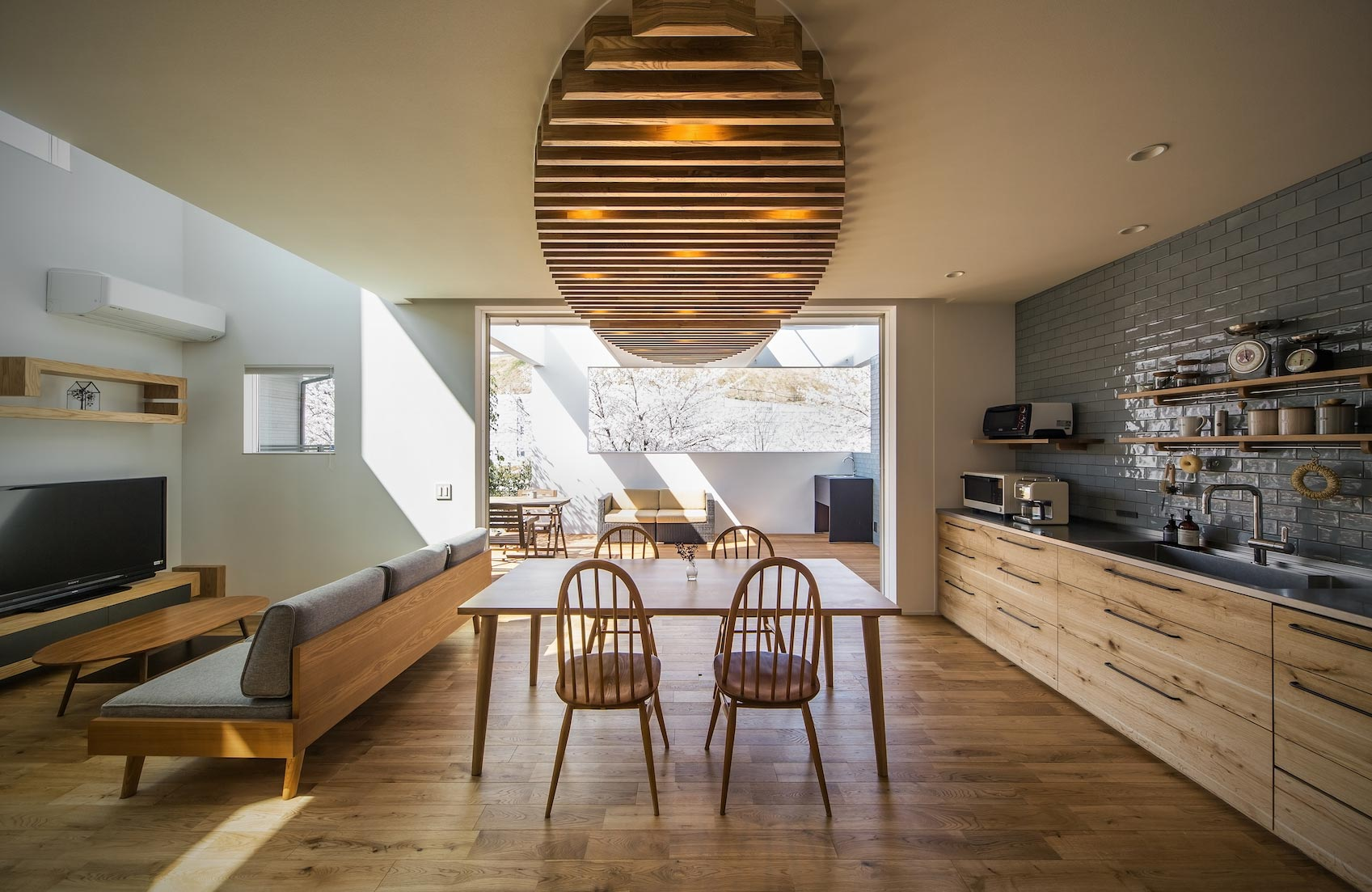 <p> LDKとアウトドアリビング: 長さ4mのキッチンはフルオーダーメード。扉の突板には、直線的なデザインを強調するような木目のはいった国産ナラ材を採用しました。壁面の棚はあえてオープンにし、家電も積極的にインテリアとしてとらえる考え方です </p>