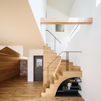 <p> LDK: 階段の下部は丸くくりぬいて軽やかな印象に。つくりつけの飾り棚は照明によって演出されています。左手奥のプレイコーナーの壁面にはおもちゃの収納棚が隠れています。書斎の扉も同様にレッドシダーの壁面のなかに。 </p>