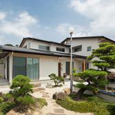 <p> 庭から住宅を見る: 低勾配の屋根でボリュームを抑え、2階部分を奥にずらすことで奥行き感をだしています </p>