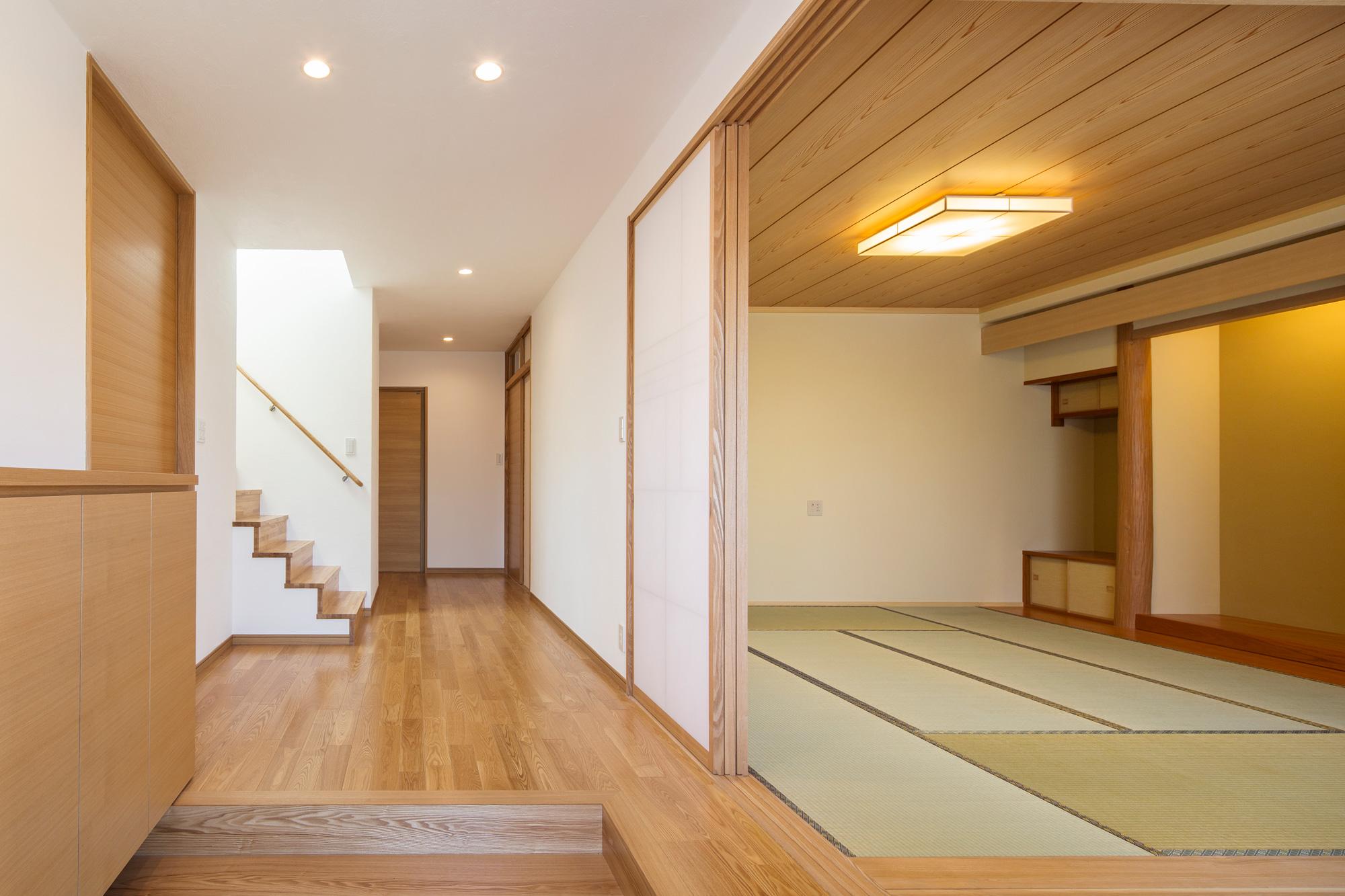 親世帯の玄関: 障子を開け放つことで和室と玄関が一体となる、昔ながらの間取り