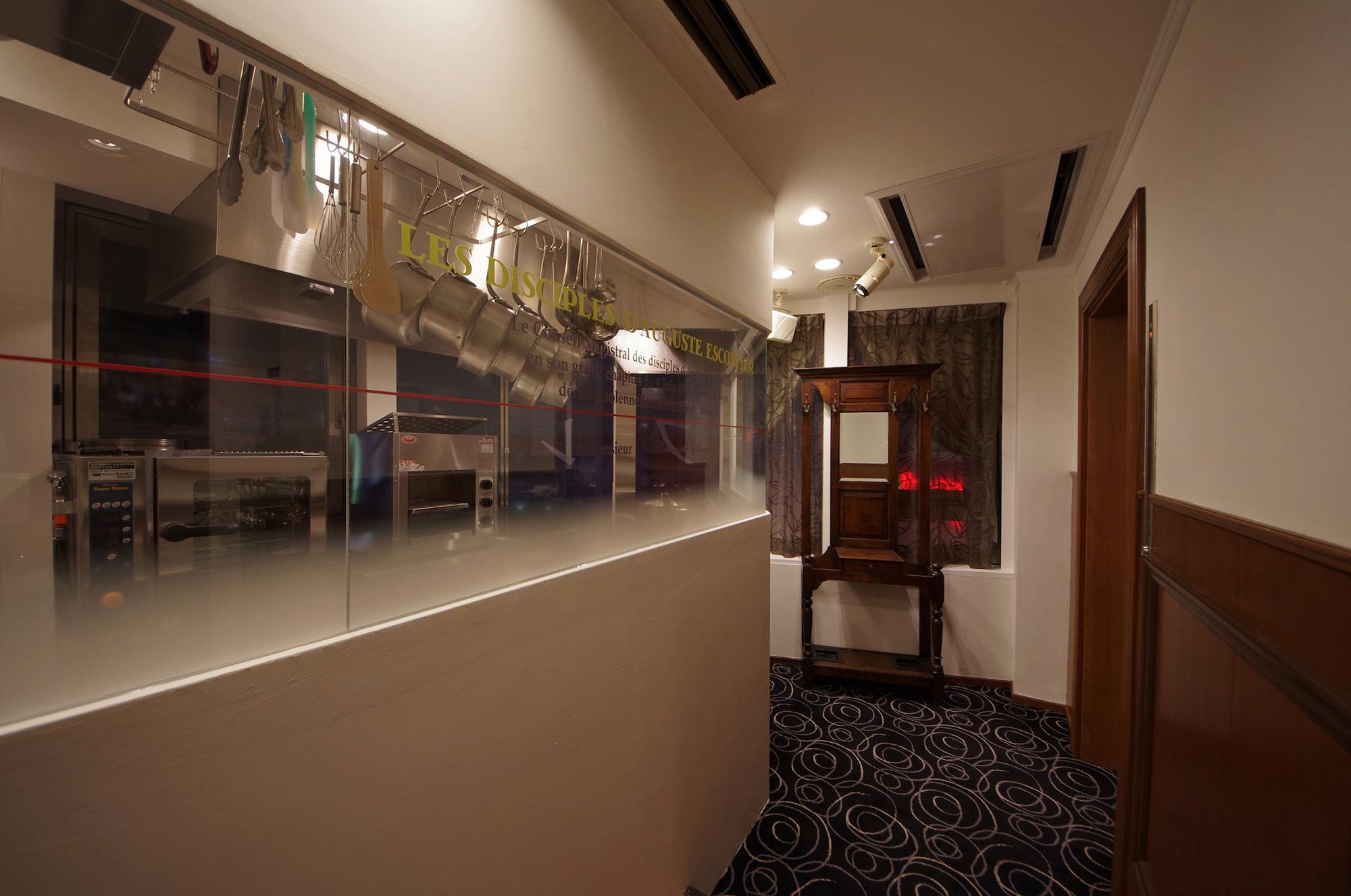 オープンキッチンとエントランス: クラシックな家具と白いモダンな壁が調和しています