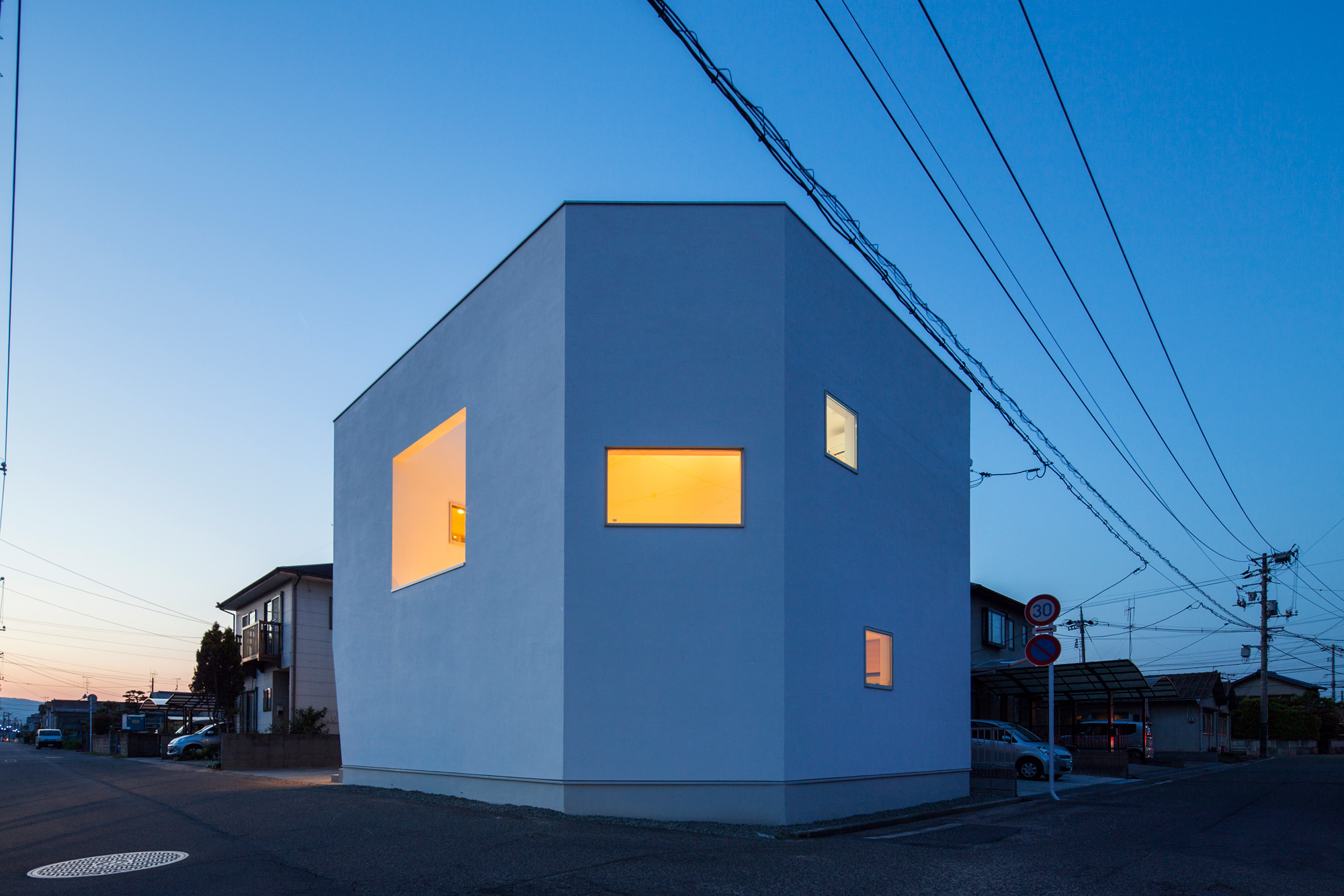 外観夕景:白い壁にリズミカル明けられた開口部からもれる、内部の光