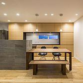 <p> リビングからキッチン・ダイニングを見る:タモの床や壁面収納と、キッチンを囲む石貼りの対比が印象的 </p>