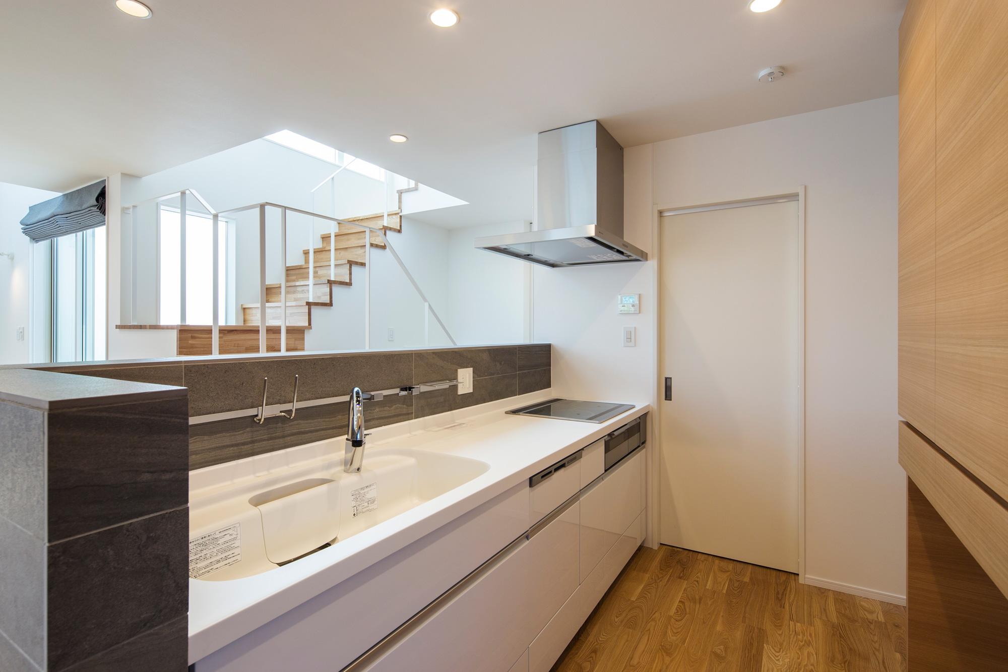 キッチン:キッチンは手元が隠れる石の壁に囲まれています。階段越しに中庭と青い空が見えます。奥の扉はパントリーです