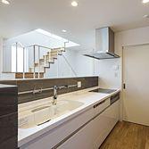 <p> キッチン:キッチンは手元が隠れる石の壁に囲まれています。階段越しに中庭と青い空が見えます。奥の扉はパントリーです </p>