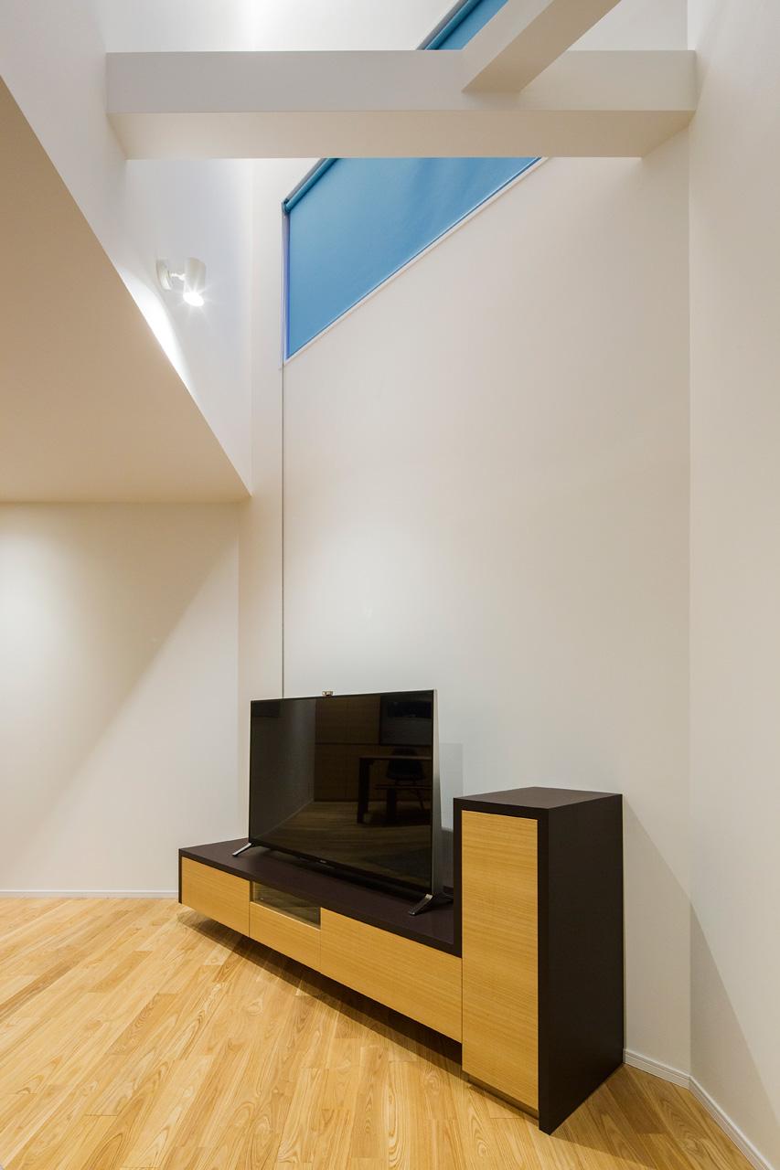リビング:造りつけのテレビボード。街路に面した開口にはさまざまな色のロールカーテンを配しています