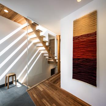 <p> エントランス:地階の駐車場から直接玄関へ上がれる階段があります。クレバスからの光を遮らないように、廊下との仕切りはガラス製です </p>