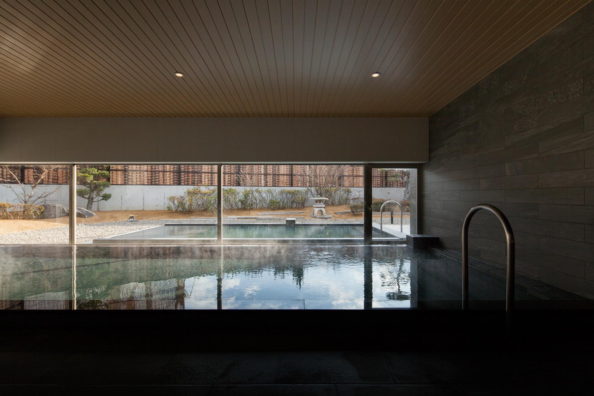 内部から外を見通す: 内湯と外湯が視覚的に連続するようにデザイン。石の壁も外部まで貫通することで連続性を強調しています