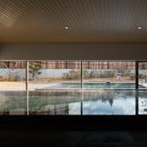 <p> 内部から外を見通す: 内湯と外湯が視覚的に連続するようにデザイン。石の壁も外部まで貫通することで連続性を強調しています </p>