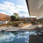 <p> 庭園と外湯: 広く計画された庭園によって切り取られた広い空が印象的 </p>