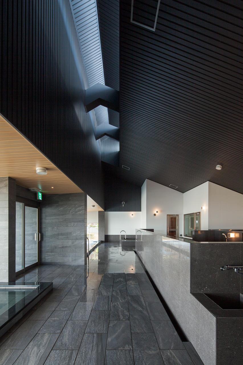 洗い場: 内湯に対して洗い場は天井を高くなっています。天窓からの優しい光が落ちてくる空間です