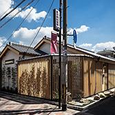 <p> 北西からのぞむ: 低い屋根と木製の縦格子が特徴的なデザイン </p>