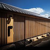 <p> 西面ファサード: デザインのアクセントとなっている縦格子の塀は光と風を通しながら適度にプライバシーを保ってくれます。街路からの視線があることで高い防犯効果も期待できます </p>