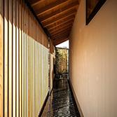 <p> 玄関口からエントランス方面をのぞむ: 内と外の間にある空間。差しこむ光がうつくしい陰影をつくりだします。その奥には[格子とヤマボウシの庭]が </p>
